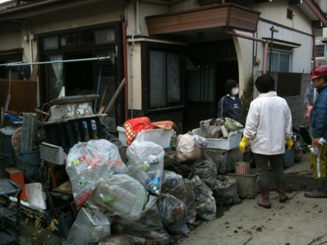 泥出しや清掃作業が終わったあとのごみや瓦礫の山、石巻市 写真:パタゴニア日本支社
