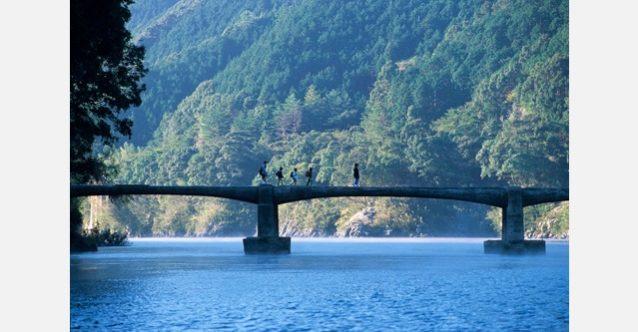 川霧が漂う朝、沈下橋を渡って学校へ向かう子どもたちの元気のよい声が響く。四万十川 写真:村山 嘉昭