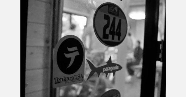 「プチビラ MTおんたけ」の食堂のドアに貼られたパタゴニアのステッカーとテンカラUSAのステッカー。Photo: Daniel W. Galhardo
