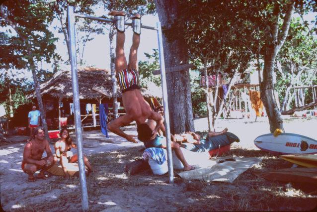 G-LANDのサーフキャンプの初期。鉄棒で逆さになっているマイク・ボヤム、女の子の横にしゃがむスパーク・ロングリー、クーラーの上に横たわってリック・ソードにロルフィングを受ける僕。背景にいるのは日本人サーファーのヤスノリ・カカイ。Photo:Dick Hoole