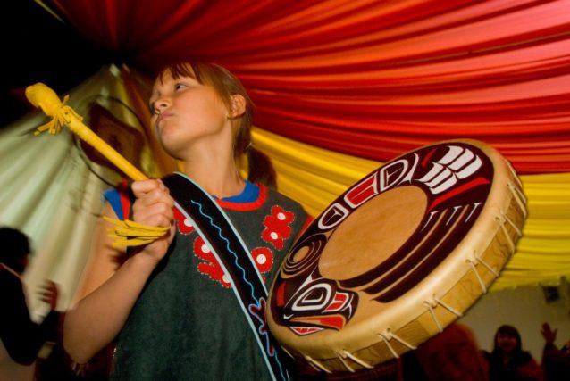 タールタン宣言100周年を祝ってドラムを叩くタールタン族の若い娘。ブリティッシュ・コロンビア、タールタン・ネーションのテレグラグ・クリークにて。Photo: Paul Colangelo