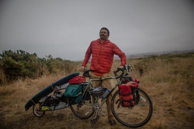自転車を地面から3センチ持ち上げてみる僕。自分の装備が何キロなのか(予想はきっと450キロ。…それくらいに感じる)、これまでに何キロ走ったのかわからない。地元で旅をするのはとても楽しい。Photo: Kanoa, Kellen, Dan