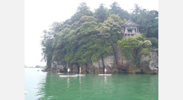 琵琶湖に浮かぶ沖ノ島まで友人に連れられて漕いで渡った。陸路からは行けない神社や海苔の養殖、琵琶鱒の漁をしている船を横目にたどり着いた島は、いい意味で時代に取り残された、時間が止まっているかのような佇まい。船で何かが届くと町内にアナウンスが入り、運ぶのを手伝える人を募って、みんなが集まってくる。木造の小学校、小さな畑や港、蛍光灯や五右衛門風呂、土間や引き戸のある家、桟橋から水に飛び込んで遊ぶ子供たち、昔は当たり前にあったものがとても新鮮に見えたことがちょっと寂しく感じたりもした。〈沖の島ツアーPUKAPUKA〉写真:白井和夫