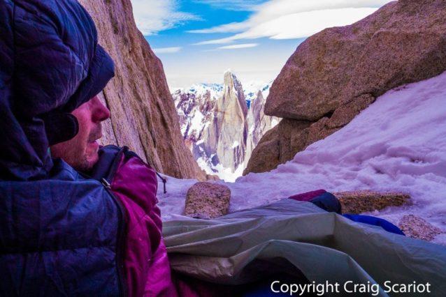 フィッツ・ロイ半ば、2日目のビバークで凍えた数時間のあと、士気を高めようとするケリー。セロ・トーレが背後にそびえ立つ。Photo: Craig Scariot