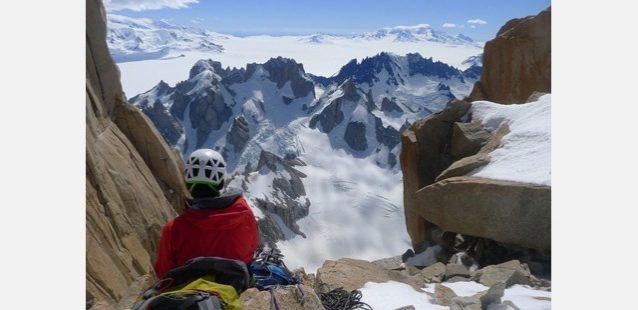 北ピラーの頂上でくつろぐ横山。眼下には先日登ったポローニ山群が見える。写真:増本 亮