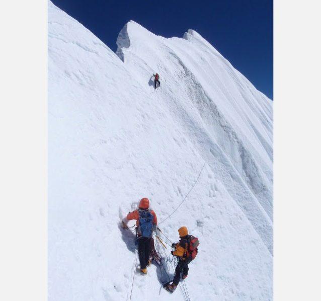 2009年ネムジュン(7139m)頂上に向けてヒマラヤ襞の稜線を進む。クライミングする花谷とビレイする田辺(右下)撮影:大木信介