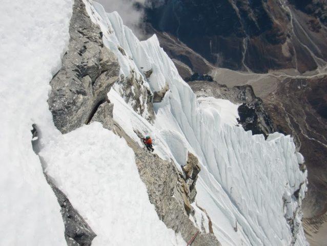 2012年キャシャール6日目頂上直下の岩壁のフォロー準備をする花谷。背後のリッジが5日目に越えてきた部分。撮影:馬目弘仁