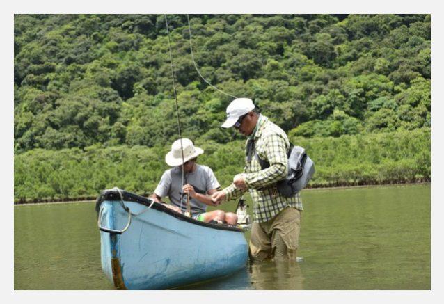 仲間達が帰京後に永井くんとの釣りを楽しんだ。マングローブの水際で相棒としばし休憩。永井くんに指示を仰ぎ、フライをセレクトする。写真:北島 清隆