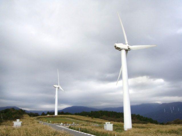 曇り空のなか、勢いよく回転する伊豆町の町営風車。右奥の山肌に小さく見える白い柱は、熱川の風車。写真:寺倉聡子