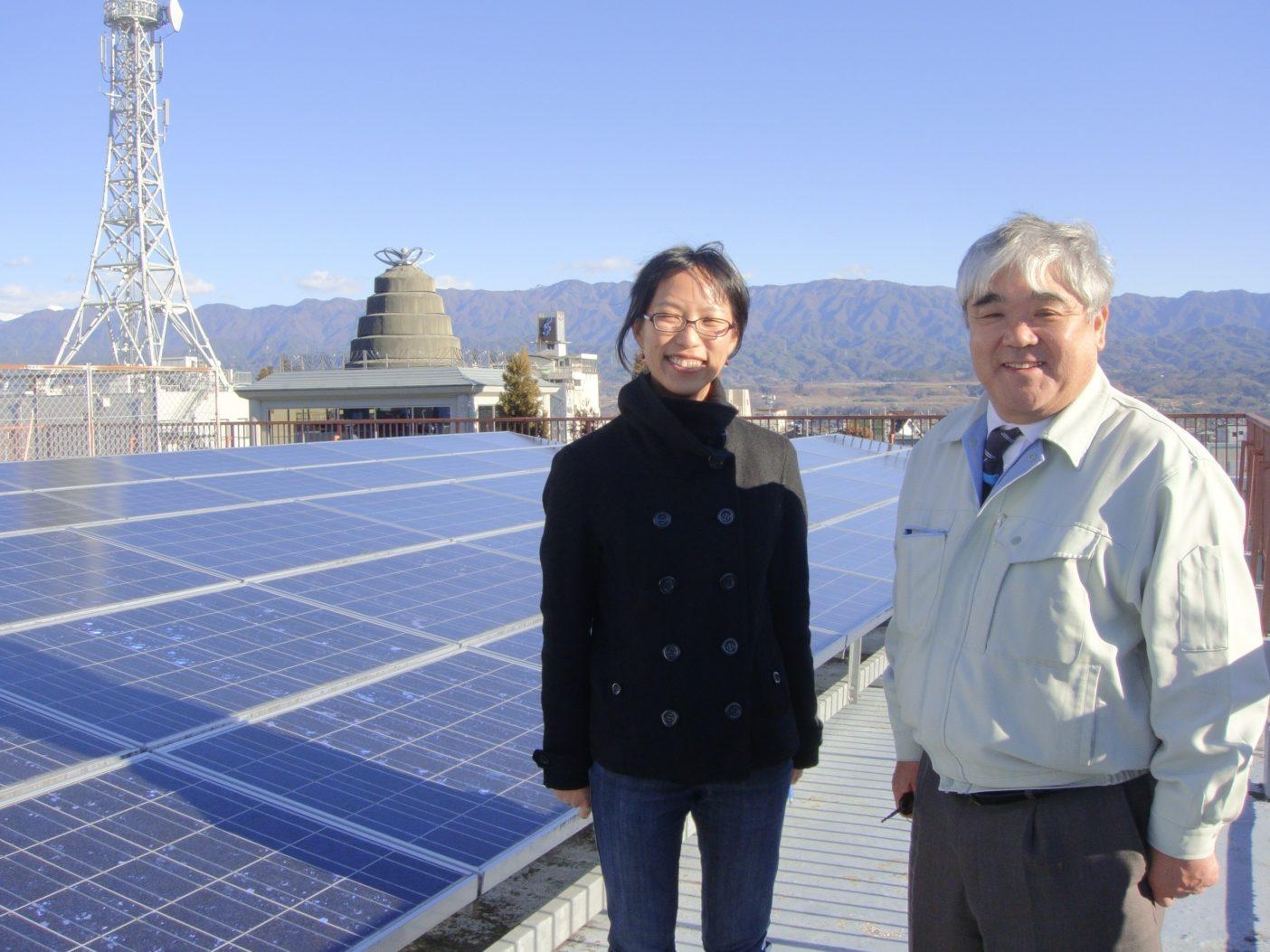長野県飯田市公民館の屋上のソーラーパネル。「おひさま進歩エネルギー」の原さん(右)とグリーンピース・ジャパンの高田さん(左) 。写真:寺倉聡子