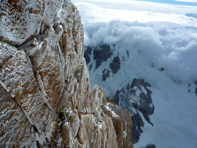 パタゴニアの南氷冠に雲が入り込む中、「スーパーカナレタ」の最終ピッチをビレイするディラン・ジョンソン。Photo: Colin Haley