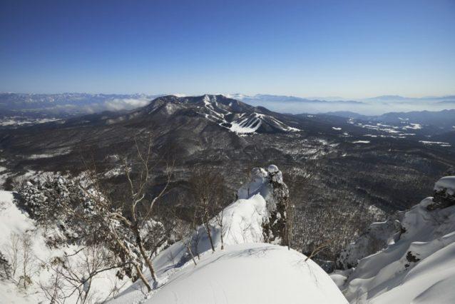 九頭龍山頂より戸隠スキー場、右に南アルプス、富士山を望む。手前から伸びる尾根から最後の下見をする2人。奥:狩野、手前:島田。写真:松尾憲二郎