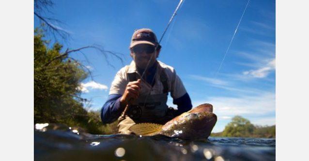 お気に入りの#2ウエイトのフライロッドで数多く生息するアルゼンチン・トラウトの1匹を釣り上げようとしているトゥキー。写真:RC・コーン提供