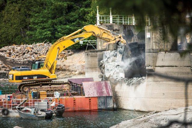 艀の上に据え付けられた掘削機が上の写真のグラインズ・キャニオン・ダムを削る。米国史上最大のダム撤去だ。ワシントン州オリンピック国立公園のエルワ・リバー。映画『ダムネーション』のシーンから。Photo: Ben Knight