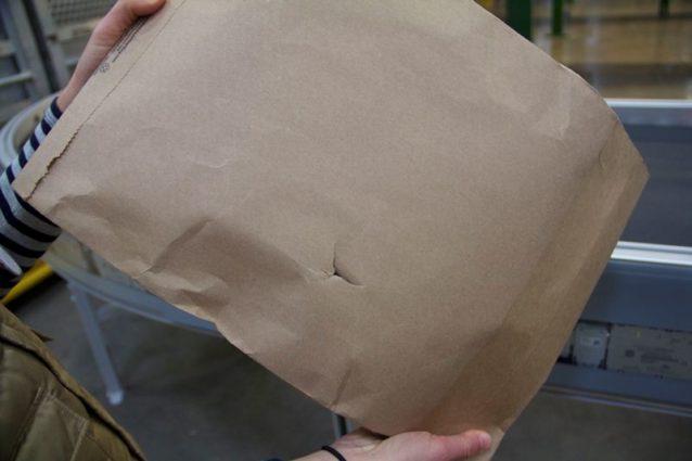 このような穴が開いてしまっては、プラスチック袋で梱包されていない衣類が輸送中に汚れてしまう可能性がある。Photo: Nellie Cohen