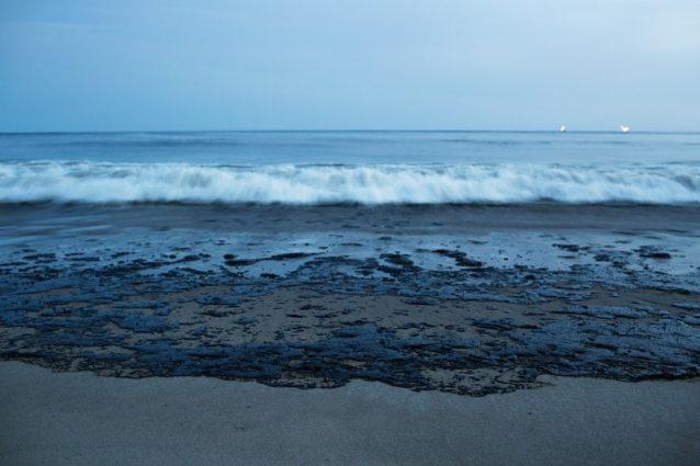 水平線に海洋掘削ドリルが光るなか、原油がビーチへと流れていく。Photo: Erin Feinblatt