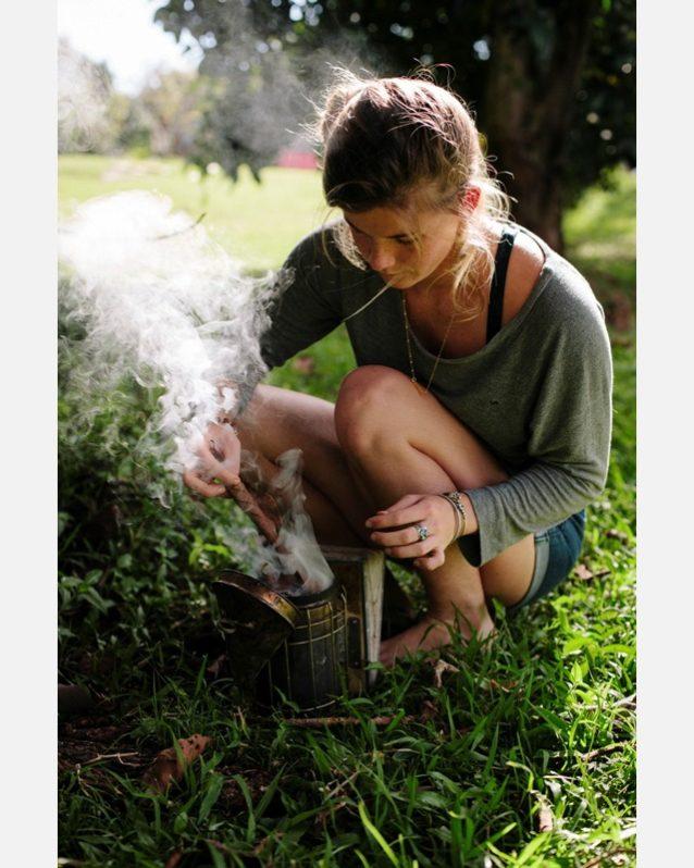燻煙器に火をつけるマリア。ハチの巣の周りに煙が広がると、ハチは巣がつぶされるのだと勘違いする。そうすると人を攻撃するのではなく、避難準備としてハチミツを蓄え、コロニーを移動する。ミツの食べすぎでハチは不活発となり、攻撃性が低下するのだ。Photo:Anna Riedel