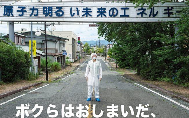 ひとけのない双葉町で、スローガンが掲げられた看板の前に立つ、防護服とマスクを身に着けた人。2011年3月、福島第一原子力発電所の事故により全町民が避難した。このスローガンは今、皮肉にも原子力への依存の危険性を思い出させている。Photo: Arkadiusz Podniesinski