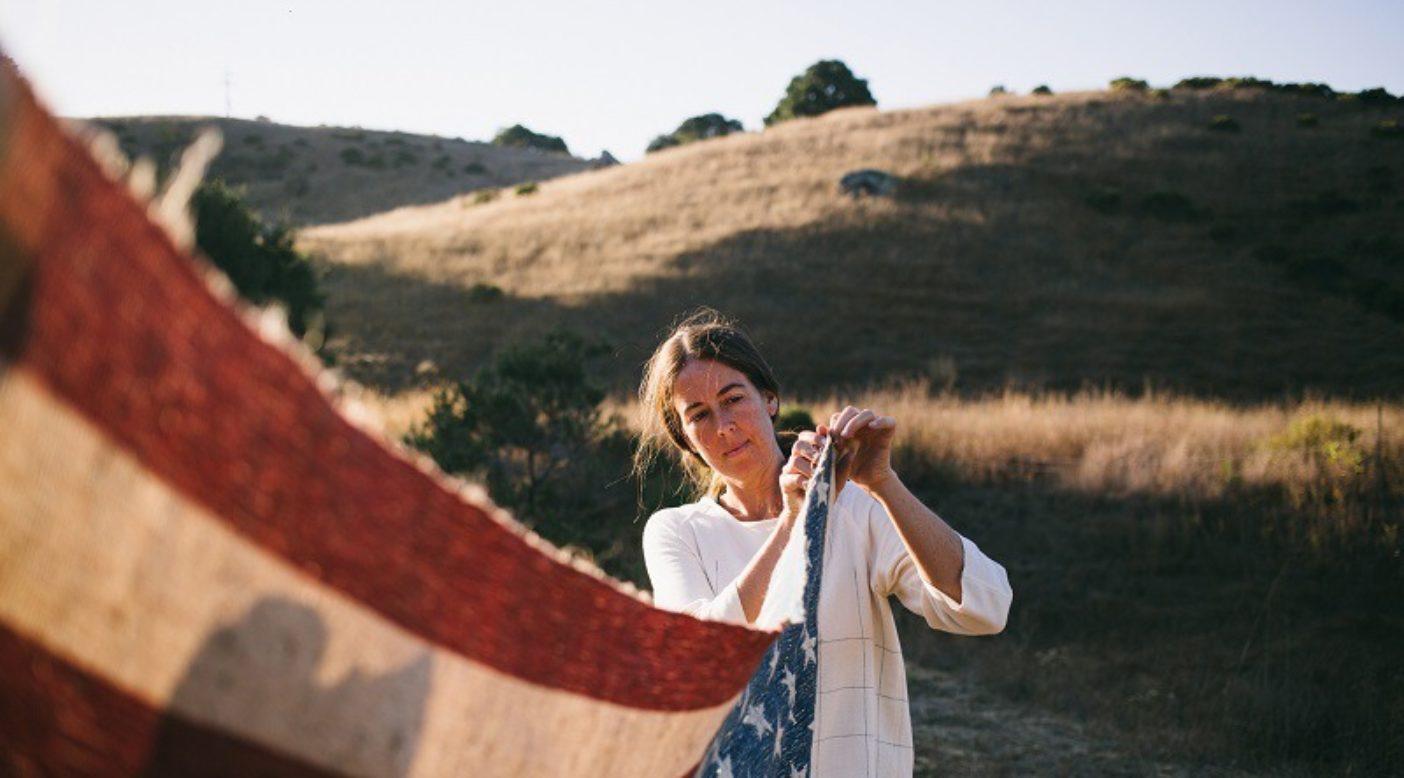 産業用ヘンプとオーガニックコットンから織られ、天然染料で染められた手製の星条旗を持つレベッカ・バージェス。Photo: Donnie Hedden