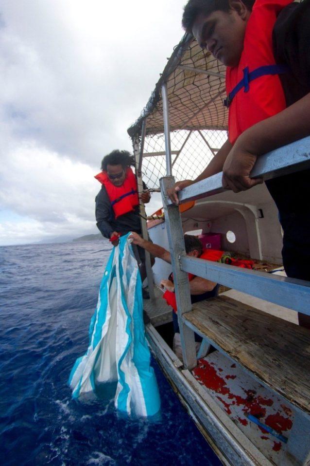 近隣の島にある学校を訪れる途中、海に漂う空気の抜けた子供用プールを拾い上げる乗組員レックス・ロケニ。Photo: John Bilderback