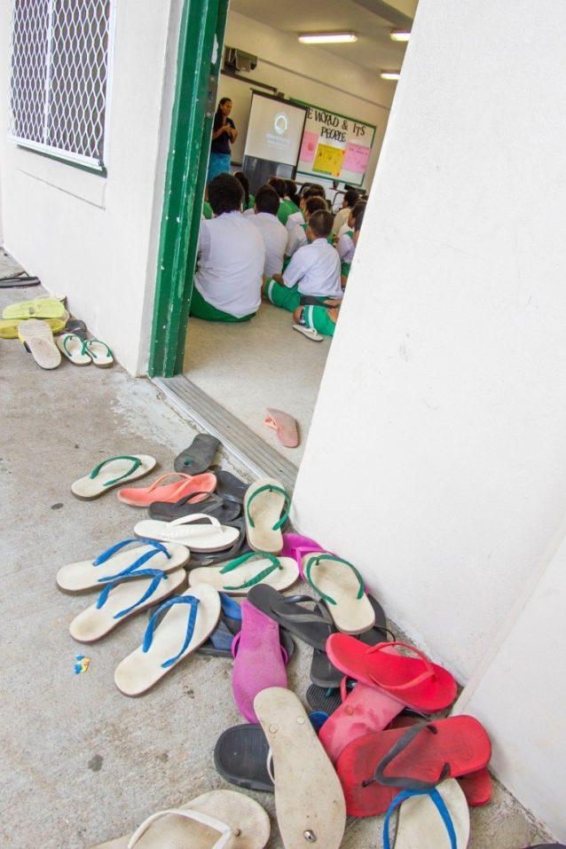 サンダルを脱いで、集中。「マラマ・ホヌア(地球を大切に)」世界航海について乗組員が語る話に熱心に耳を傾ける子供たち。Photo: John Bilderback