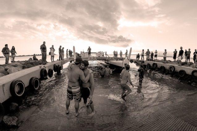 故郷の海に再進水するホクレア号の横で肩を寄せ合う乗組員。オアフ島のマリン教育トレーニングセンターにて。Photo: John Bilderback