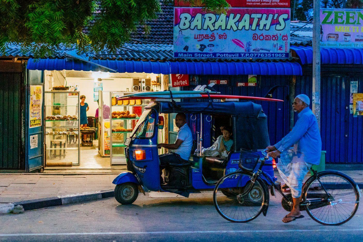 ベリンダが朝にパン屋で買い物するあいだ、トゥクトゥクで待機するレイソン。Photo: Jarrah Lynch