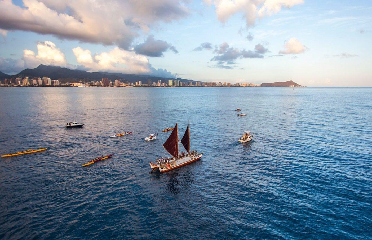 ヒロへとホノルルを発つ ホクレア号。そこでは乗組員が 世界航海の幕開けにタヒチへ 出帆する時を決める風を辛抱 強く待つ。Photo: John Bilderback