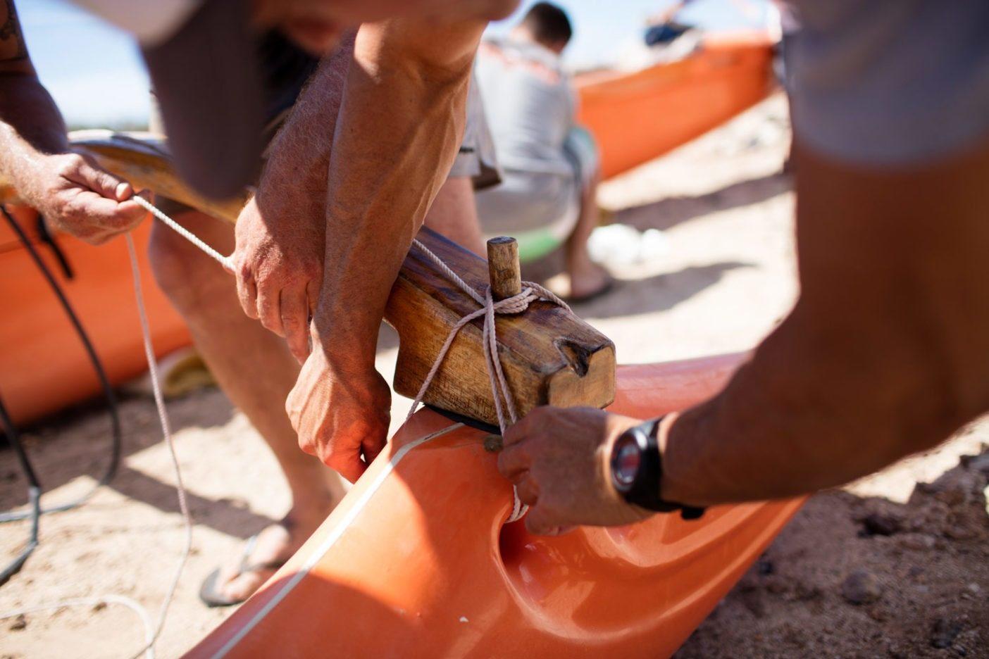 イアコ(アウトリガーの腕木)とアマ(アウトリガーの浮子)を結びつける様子。リギングにロープ類を使用するのは、「モロカイ・ホエ」の伝統的特徴を守るためのルールの1つである。Photo: Tim Davis