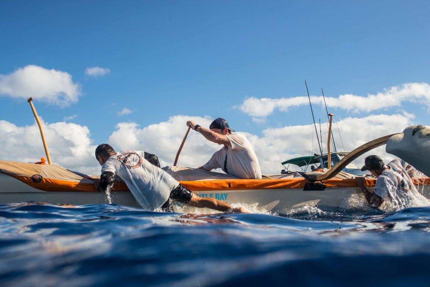 海峡の中間地点でウォーターチェンジを行う〈Bad News Bears〉のクルー。各チームは交代のパドラーを積んだボートに伴走され、カヌーにはつねに6名のパドラーが乗員する。Photo: Tim Davis