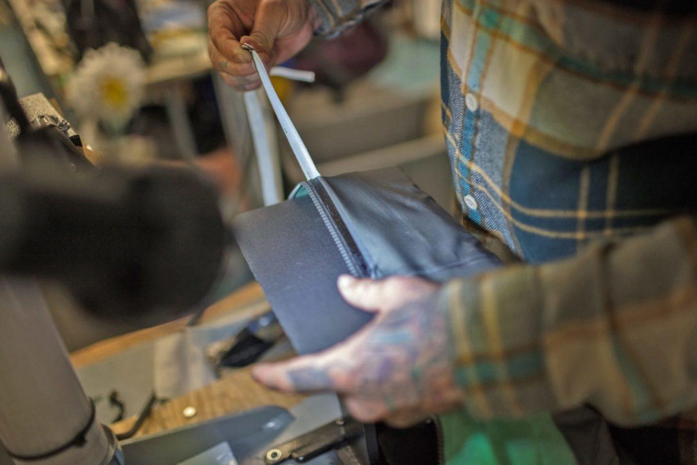 ジオ・ナイトのヒートプレス機で温めてから緩ませたあと、パウスレイヤー・ジャケットのジッパーの裏地から防水処理テープをはがすアンディ・クック。Photo: Tim Davis