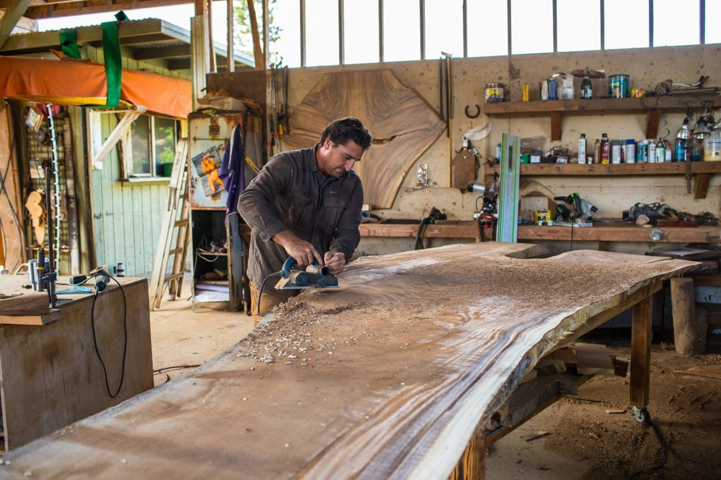 3年間乾燥させたあと、ワイメア・ベイ付近で回収した7.5メートルのアメリカネムノキの板材にカンナがけをするベン。ハワイ州ハワイ島 Photo: Tim Davis