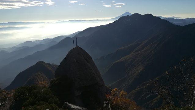 甲斐駒ヶ岳黒戸尾根を象徴する景色。岩の上に突き刺さった2本の剣と背後の鳳凰山、富士山。
