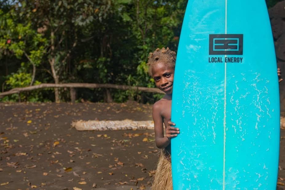 初めて見るサーフボードを手にする裸族の女の子。Photo: Yoko Nakamura