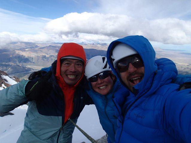 強風のアグハ・ギヨメ山頂にて。左から横山、増本さやか、増本亮。