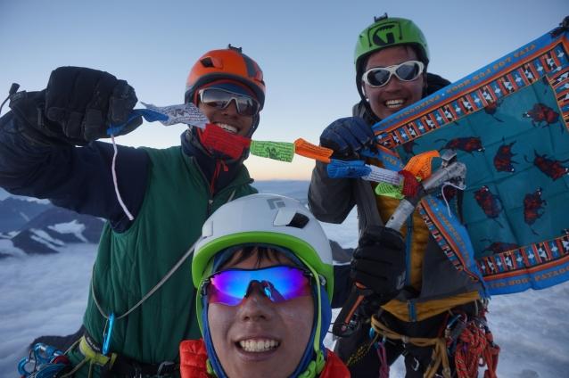 山頂にて、Viva Los Fun hogs旗とタルチョを掲げるメンバー。写真:福田倫史