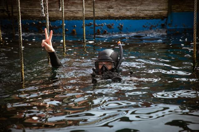 海中に下ろされたロープの横で海に入ってピースサインするダイバー