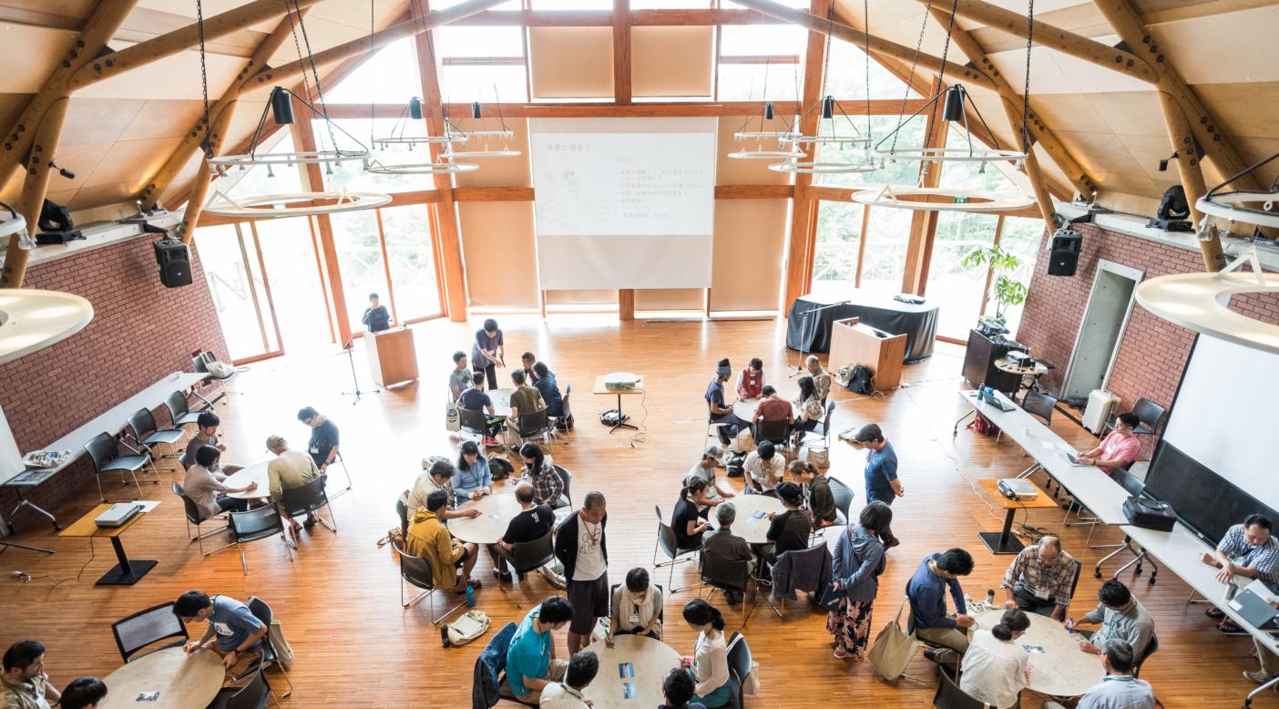 グループに分かれて、渋谷駅前(都市)と白馬村(中山間地)の、現在の課題と、課題の裏返しではないありたい未来を考え、描く。円型模造紙「えんたくん」を膝に乗せる参加者たち。 全写真:パタゴニア日本支社