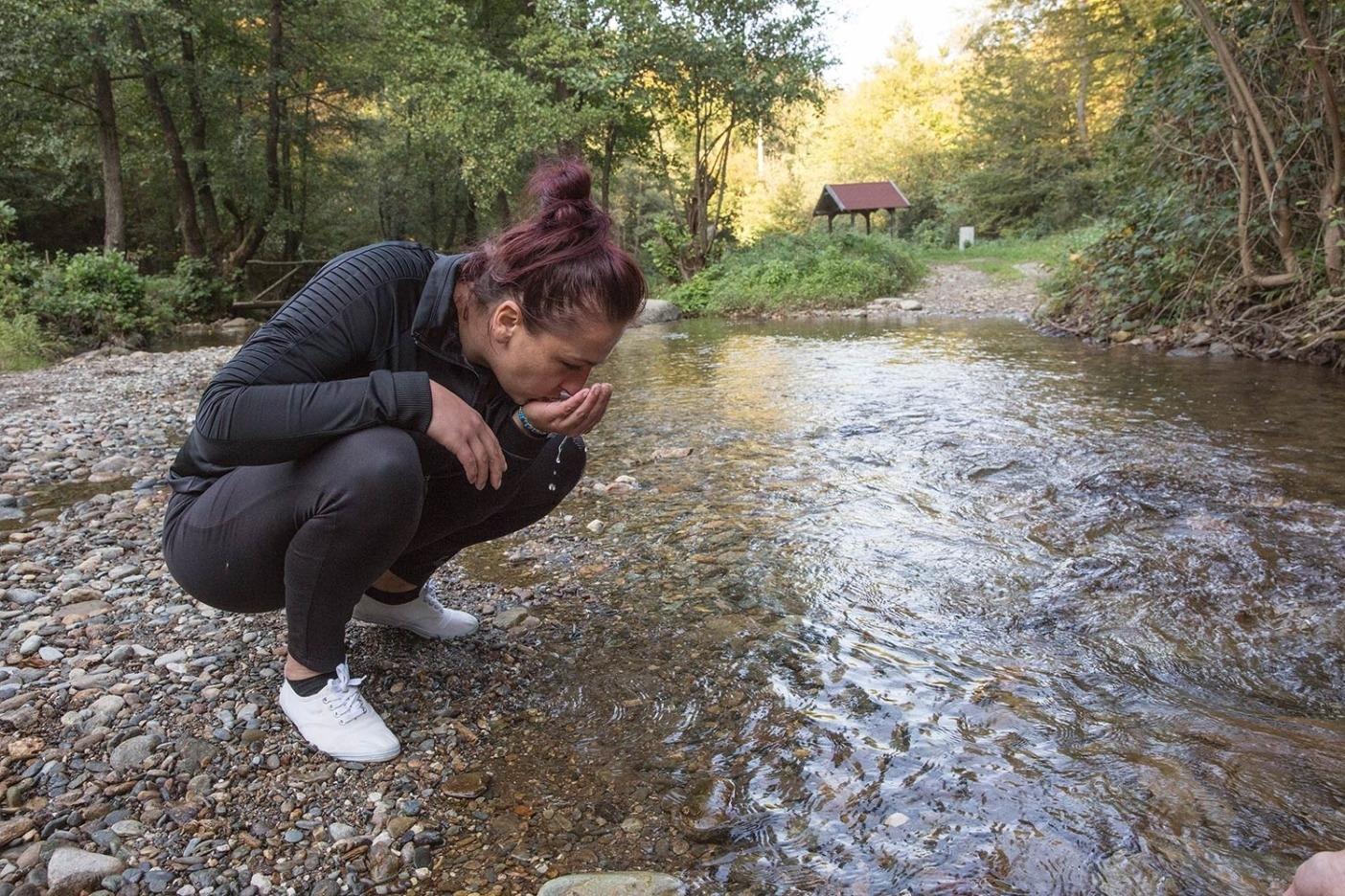 クルシュチツァ川の水を飲むことをみずから勧めるネリナ・アフミツ。分水ダム建設をめぐる闘いにおいて、もしサラエヴォの電力会社ヒグラコンが勝利を収めれば、彼女や他の地元民は この淡水源を失うことになる。Photo:Andrew Burr