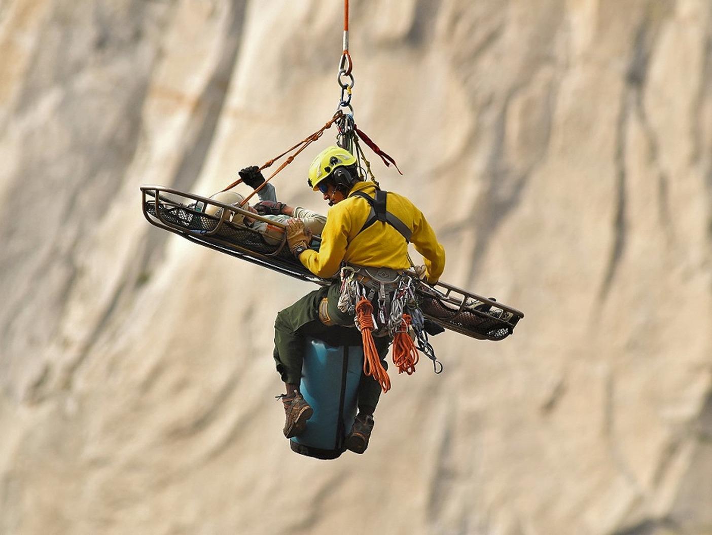 事故の直後、ヨセミテ国立公園 レンジャーのブランドン・レイサムとともにヘリコプターで谷底へと降ろされるクイン。 Photo: Tom Evans