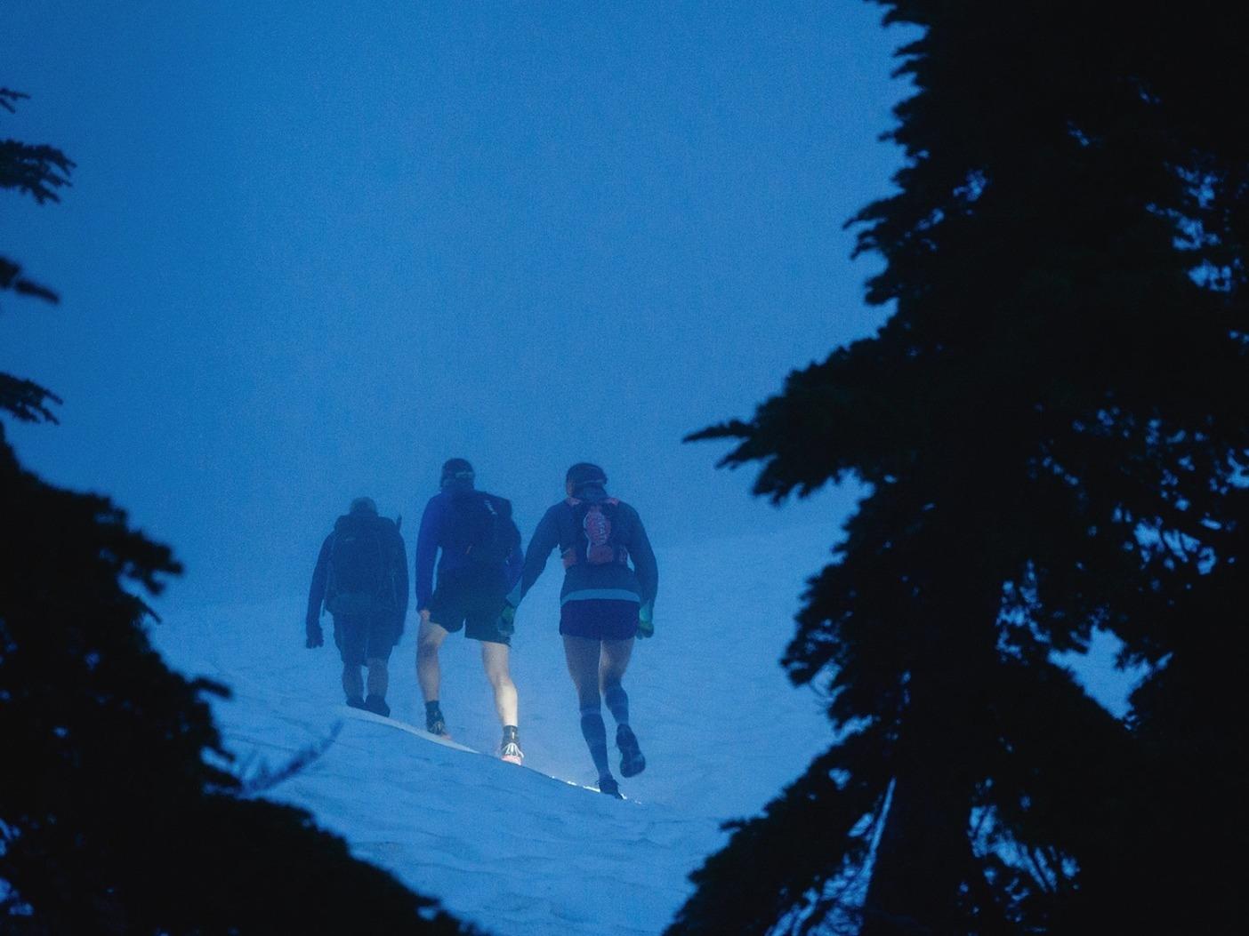 早朝の霧の中、雪を踏んで登り始めるクリッシーとジェレミー。Photo: Ben Groenhout