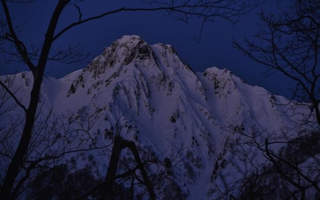 闇夜に浮かび上がる大源太山東面。Photo: AO