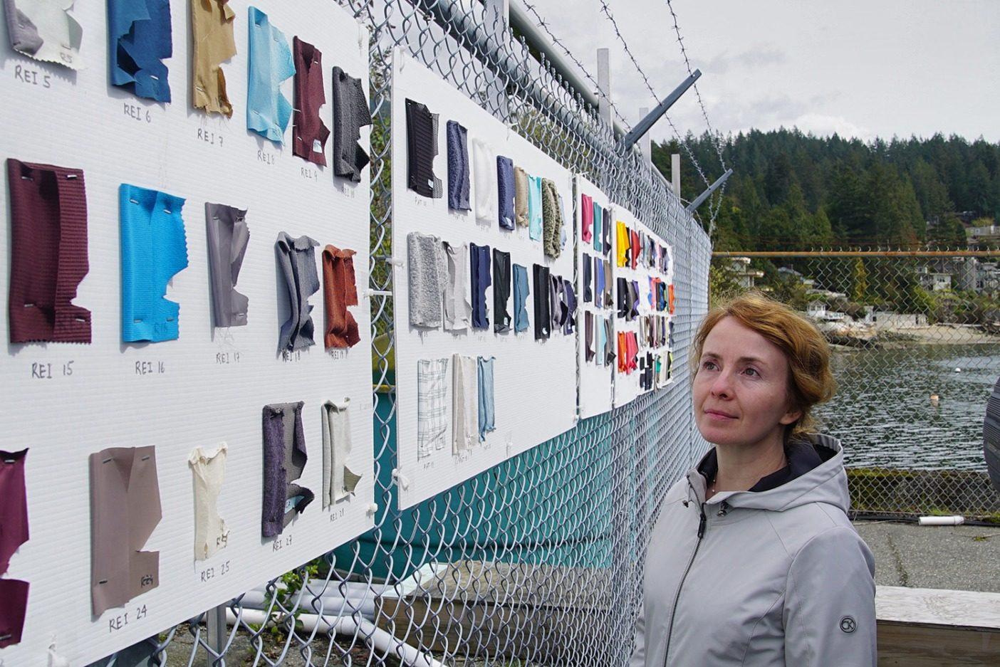 風化実験に使われた布地見本の横に立つ〈オーシャン・ワイズ〉のプラスチック・ラボのカテリナ・ヴァシェンコ。「発見するマイクロファイバーが正確にどこから来ているのかを知りたいのです。より深く理解すればするほど、その削減のために効果的な行動が起こせます」と彼女は言う。Photo: Lorand Szasz (Ocean Wise/Vancouver Aquarium提供)