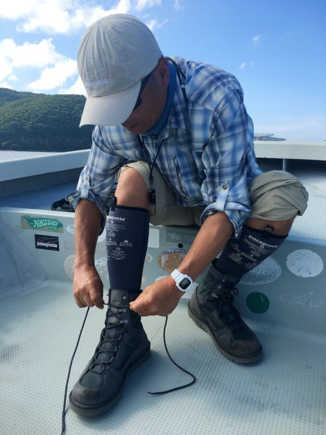 釣り場に向う船上でブーツに足を入れる瞬間は、期待感と高揚感で自然と顔がにやけてくる。 写真:中島徹也