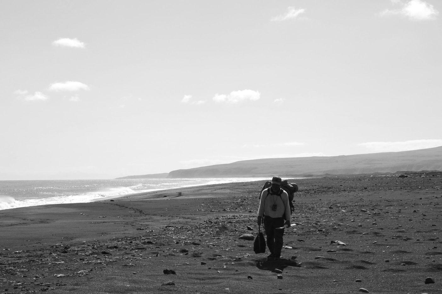 強風による停滞が続き、荷物を背負い移動する。ウムナック島にて。 写真:岩本和晃