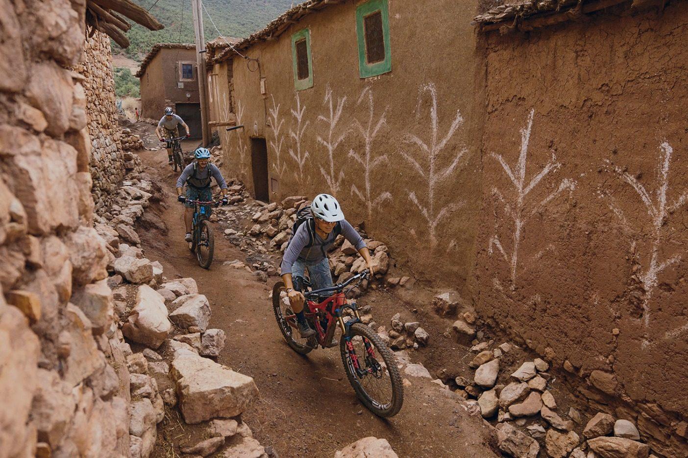 一車線道にて、前方注意。モロッコのシングルトラックの次なる区間を目指し、ドゥズルゥの村の 裏路地を縫い進むレイラニ・ブランツとピエール= アラン・レンファーとクリス・キーマイヤー。Photo: Leslie Kehmeier