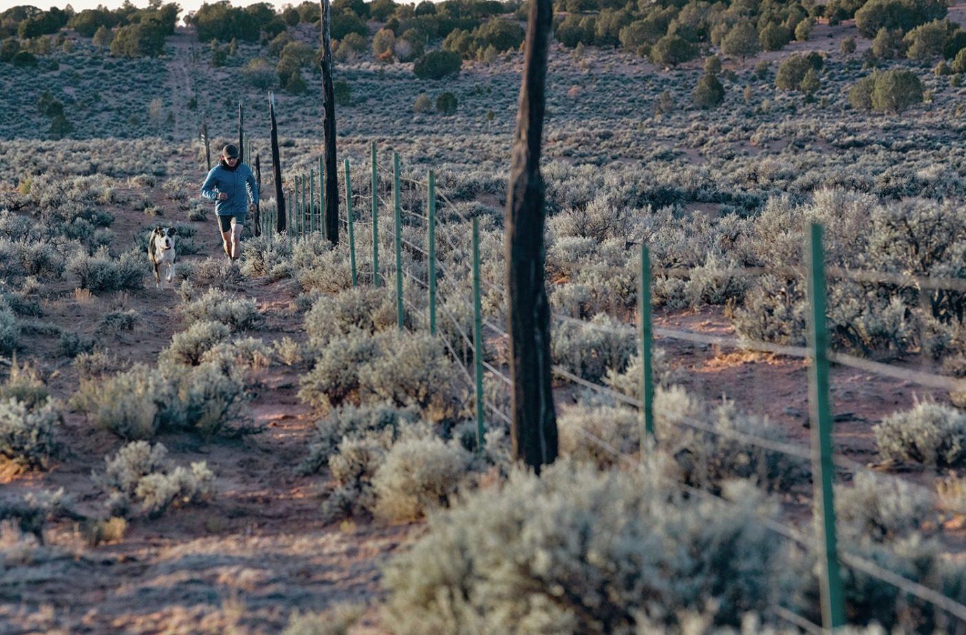 牧場を囲む柵を走りながらチェックするイーライ(と、彼のランニングパートナーである犬のトラクター)。Photo: Ace Kvale