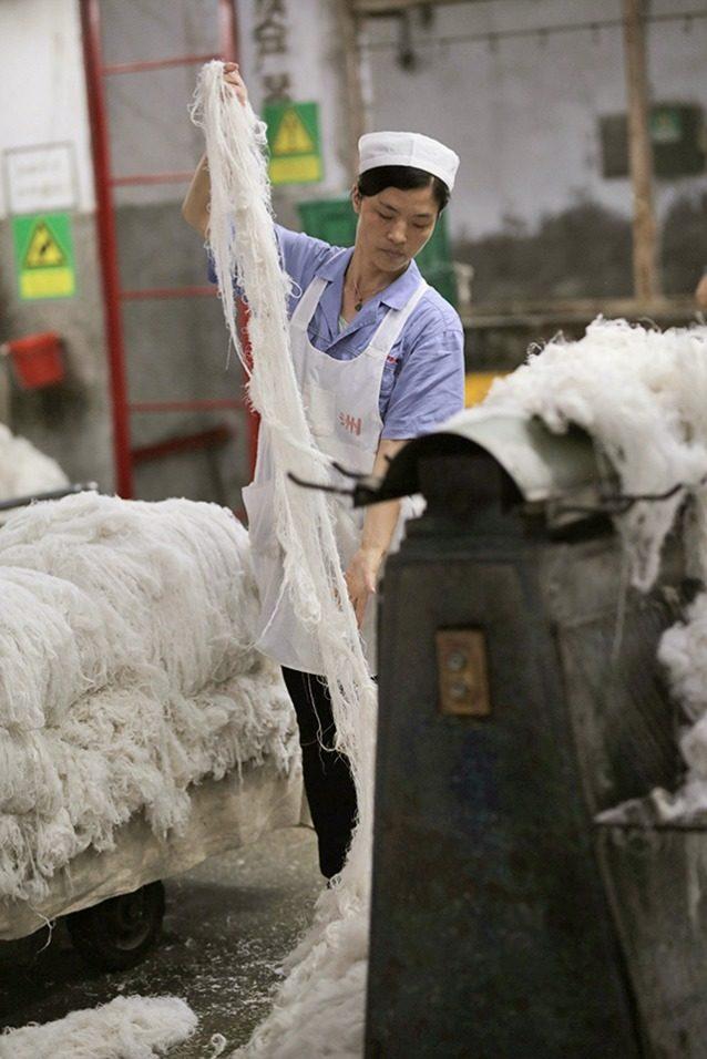 繊維は柔らかくなるまで何度も洗う必要がある。濡れた繊維の房をばらばらに引き離し、さらに房をほどく機械に通していく。 Photo: Lloyd Belcher