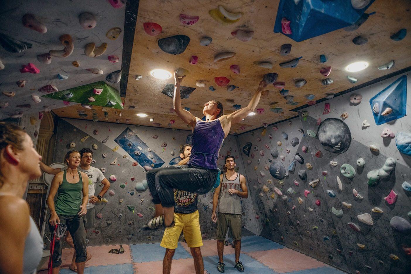 テヘランにある私営のスポーツジムで、照明に向かって登るアン・ギルバート・チェイス。アパートの地下をボルダリング用スペースに一変させている。イランのジムやクラブには公営と私営があるそうで、私営のジムでは男性と女性が一緒にクライミングやトレーニングをすることもできるが、それは公営のジムでは許されない。私営のクラブは、ある意味では、山頂での体験を街でも少し味わうことができる場所であり、たとえ山から遠く離れていても、オーガニックな人間関係やクライミングコミュニティを繁栄させることのできる場所とも言える。 Photo: Beth Wald