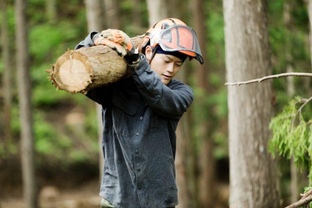 伐採した木材を運ぶ。数十キロの丸太も軽々と肩に担ぐ。写真:五十嵐 一晴